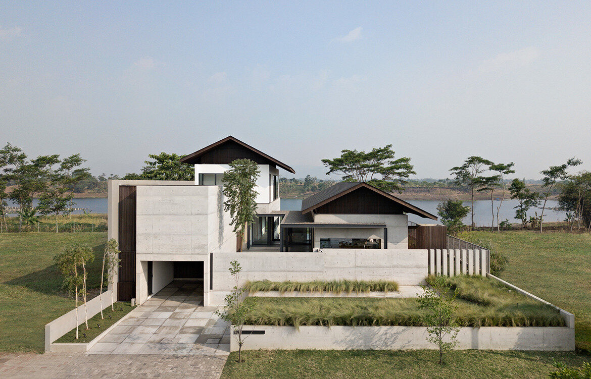 Concealed by concrete perimeter walls, the lakeside Iyashi House by Pranala Associates looks like a private garden city