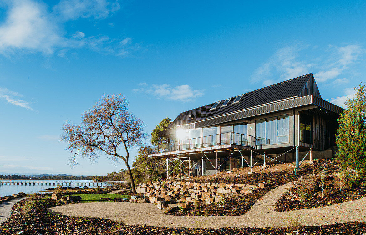 Vertical rough-sawn Tasmanian Oak clads the gabled ends and contrasts with the horizontal black Colorbond cladding on the roof and rear of The Boathouse by My Build, which coexists with the design aesthetic of neighbouring boatsheds.