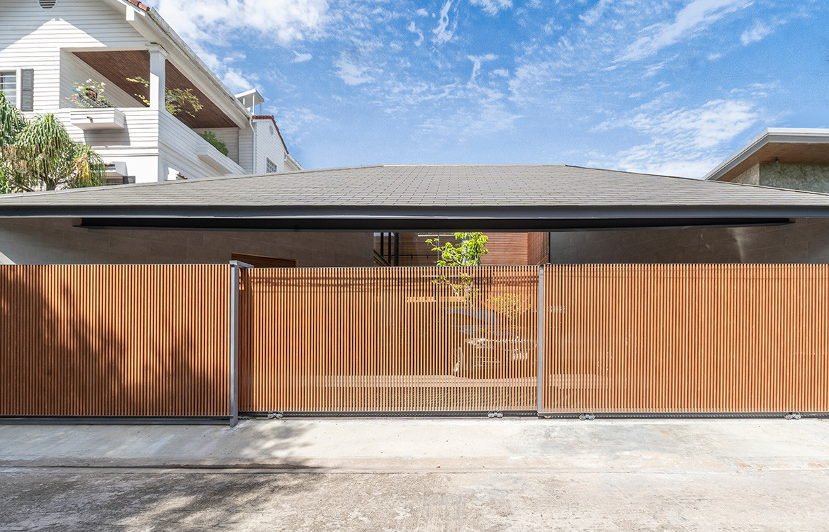 The Roof House by Looklen Architects hides behind a timber gate in a quiet residential street of Bangkok.