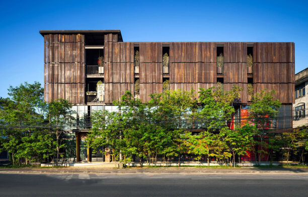 The perforated metal screens of the façade of Oui J'aime Hotel By Wallasia provide guests with privacy and sunshade during the day.