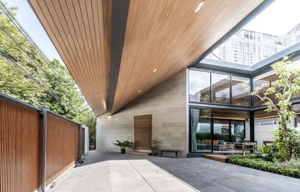The internal courtyard of The Roof House by Looklen Architects is just visible through a lath timber fence.