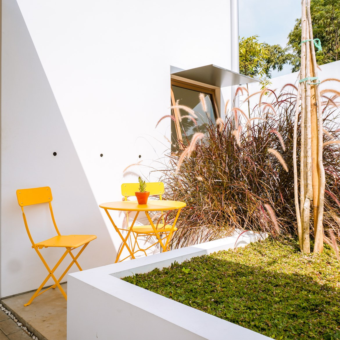 Orange chairs and table on the garden patio, in front of the white exterior of the Eureka House by Luwist Spatial.