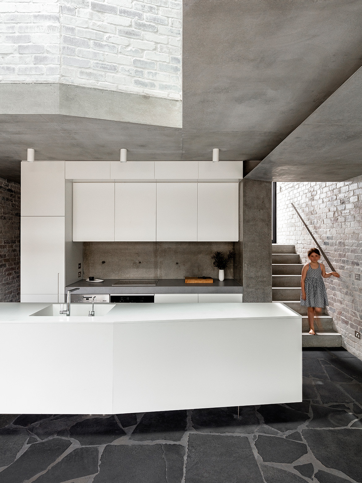 Rock-like materials and a sense of monumentality connect a new concrete pavilion with a longstanding sandstone cottage in Balmain, Sydney.