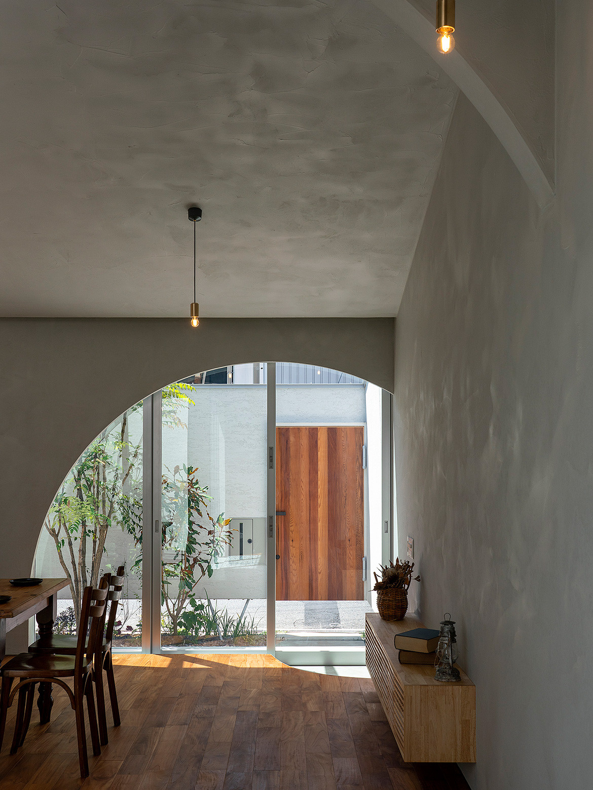 House in Ohasu by Arbol features timber floorboards, rendered concrete walls, a central courtyard, high ceilings and architectural arches.