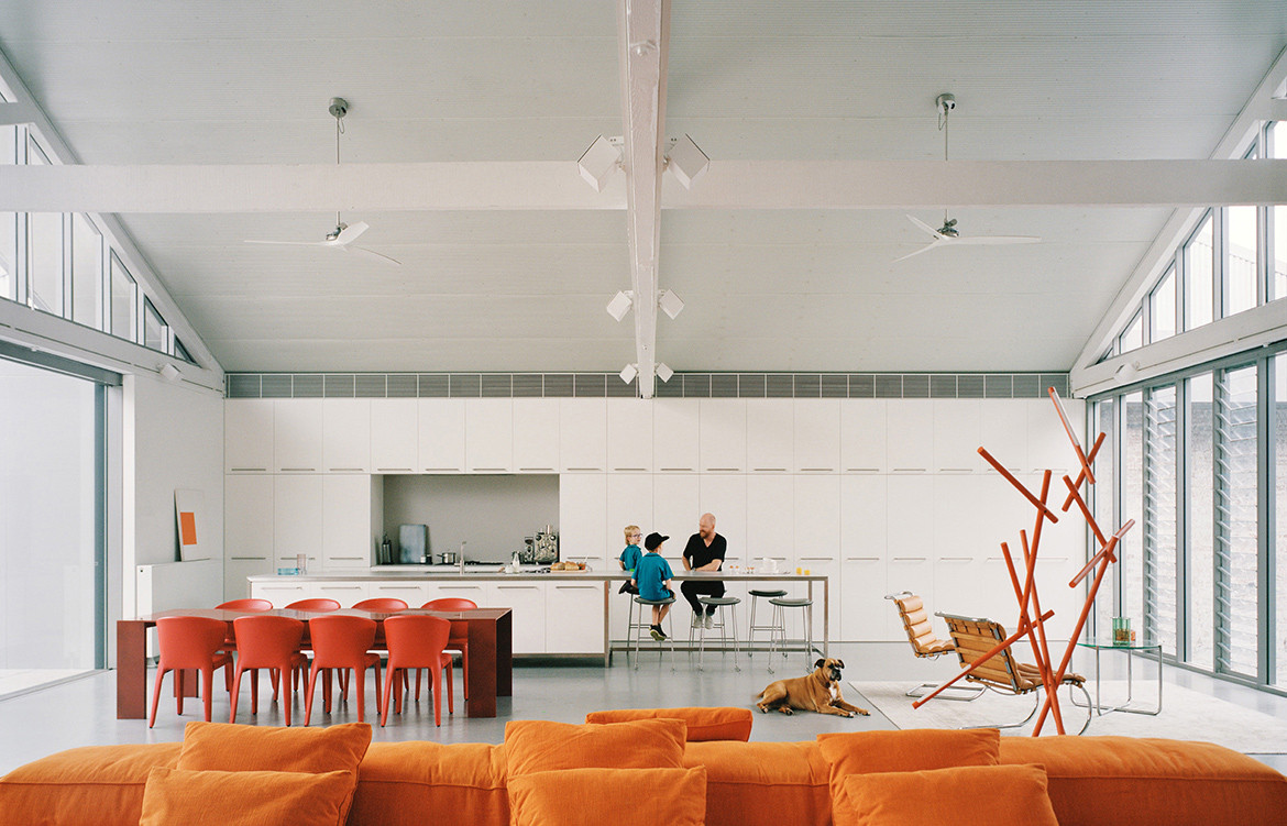 Metallico dining table by Porro adds a pop of red to the white and grey minimalist colour palette of Redfern Warehouse by Ian Moore Architects
