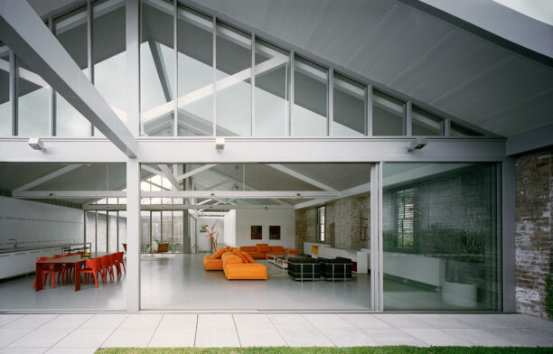 Redfern Warehouse by Ian Moore Architects has a contemporary open plan floor plan configuration and a white, grey, orange, and red colour palette
