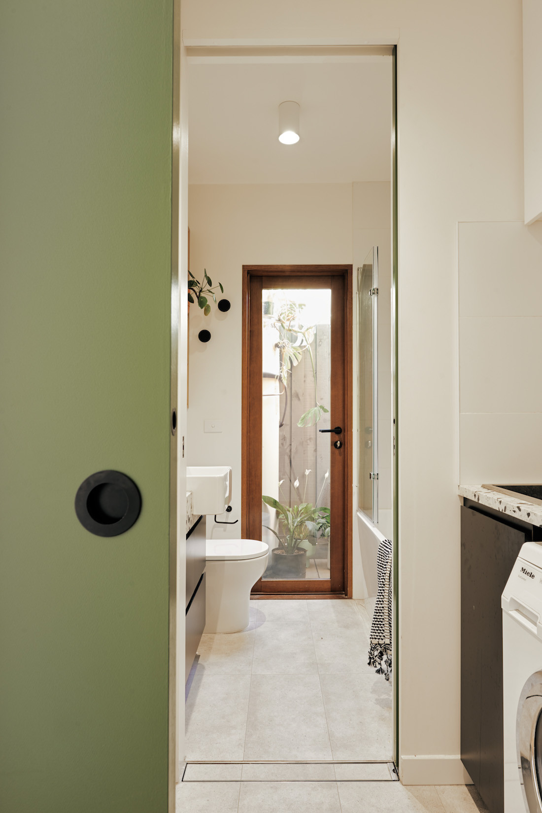 A Dulux coloured Asparagus Green sliding door between the Brunswick home's bathroom and laundry.