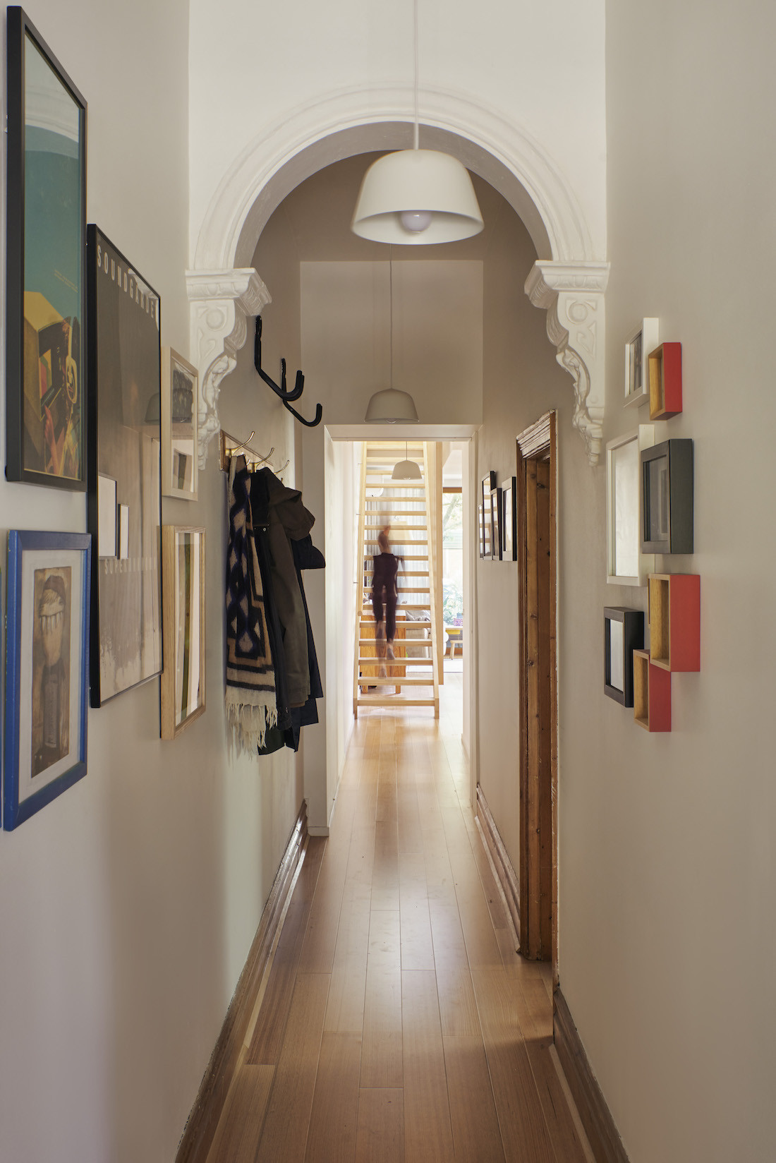 A white entrance hallway has high ceilings and an archway with photographs covering the walls.