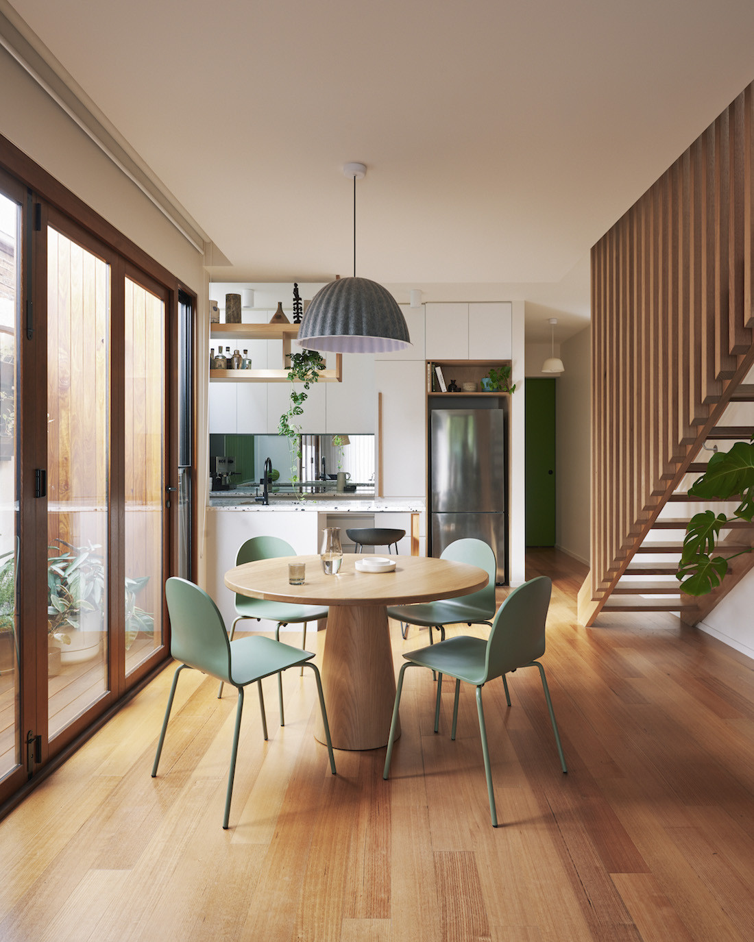 Dining table, floating staircase and kitchen of the Brunswick home.