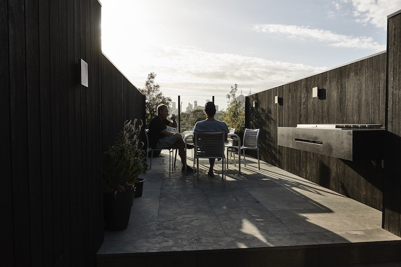 The friends sit in the sunshine on the rooftop deck of The Richmond House.