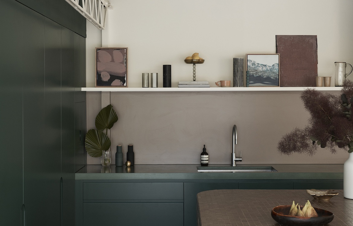 The dark green kitchen with white walls and a brown tiled mosaic island bench. Wahroonga House by Tom Mark Henry.