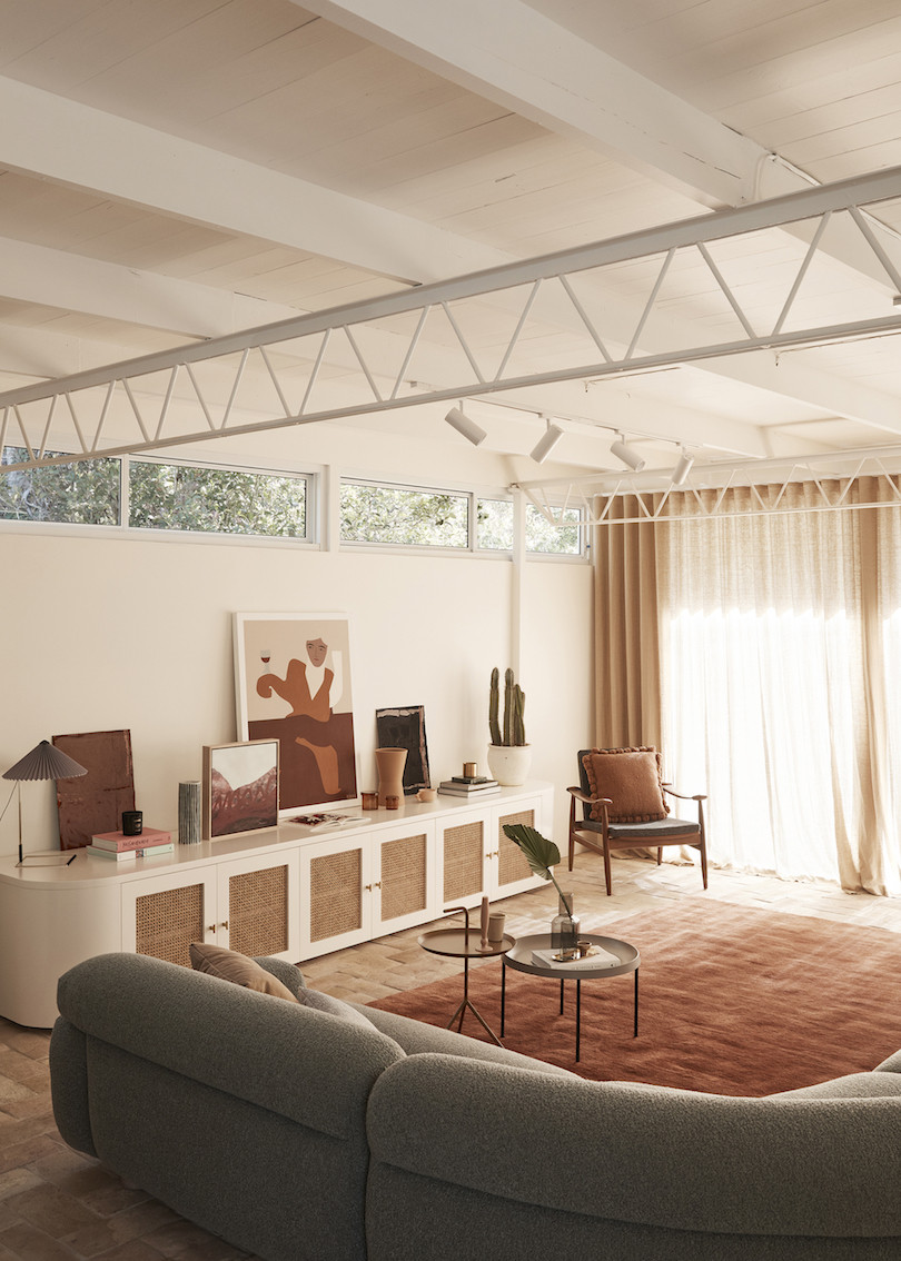 A loungroom with white walls and white timber ceiling with support trusses. Wahroonga House by Tom Mark Henry.