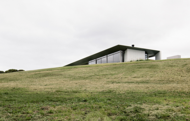 Carr Peninsular House peaks out above a grassy hill.