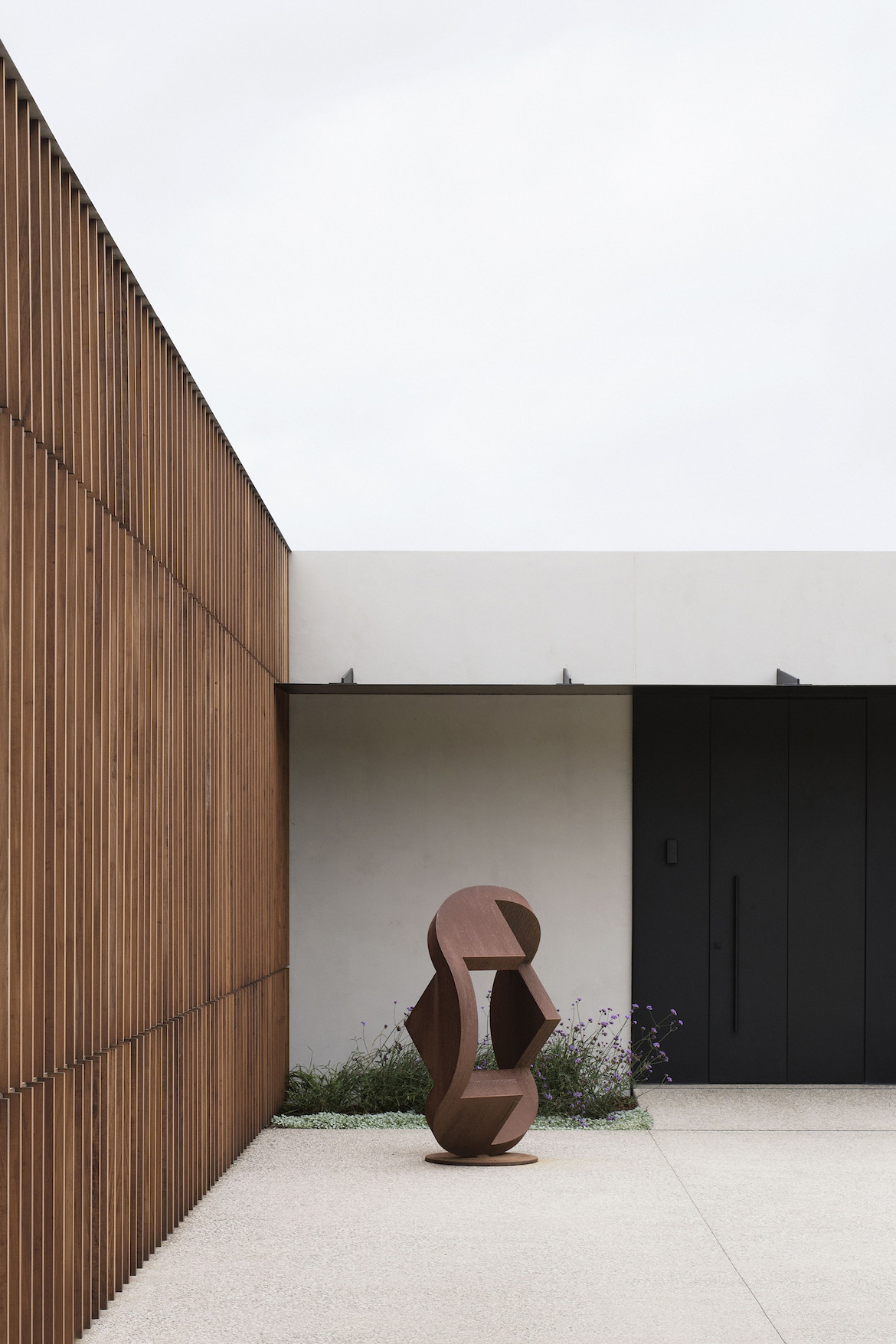 A sculpture sits outside the Peninsula House next to timber cladding.