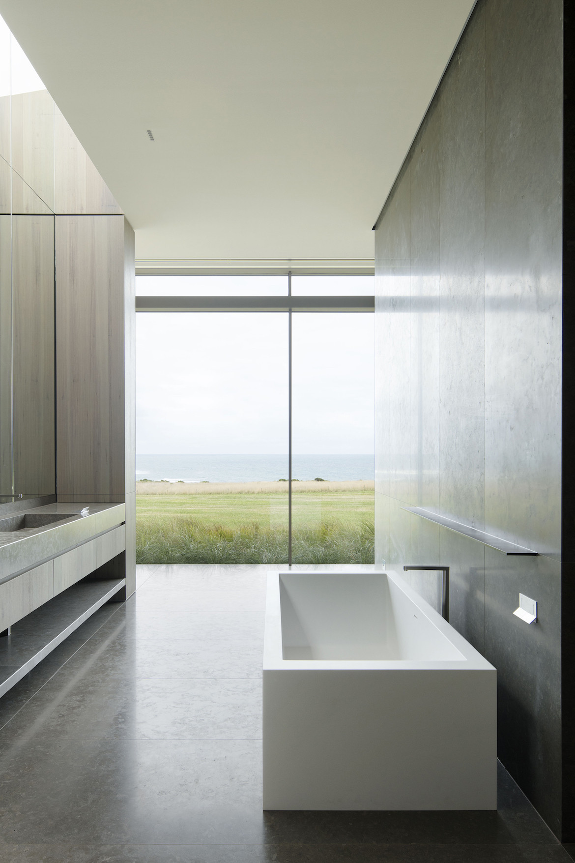 A bathtub looks through the floor-to-ceiling windows over the ocean views.