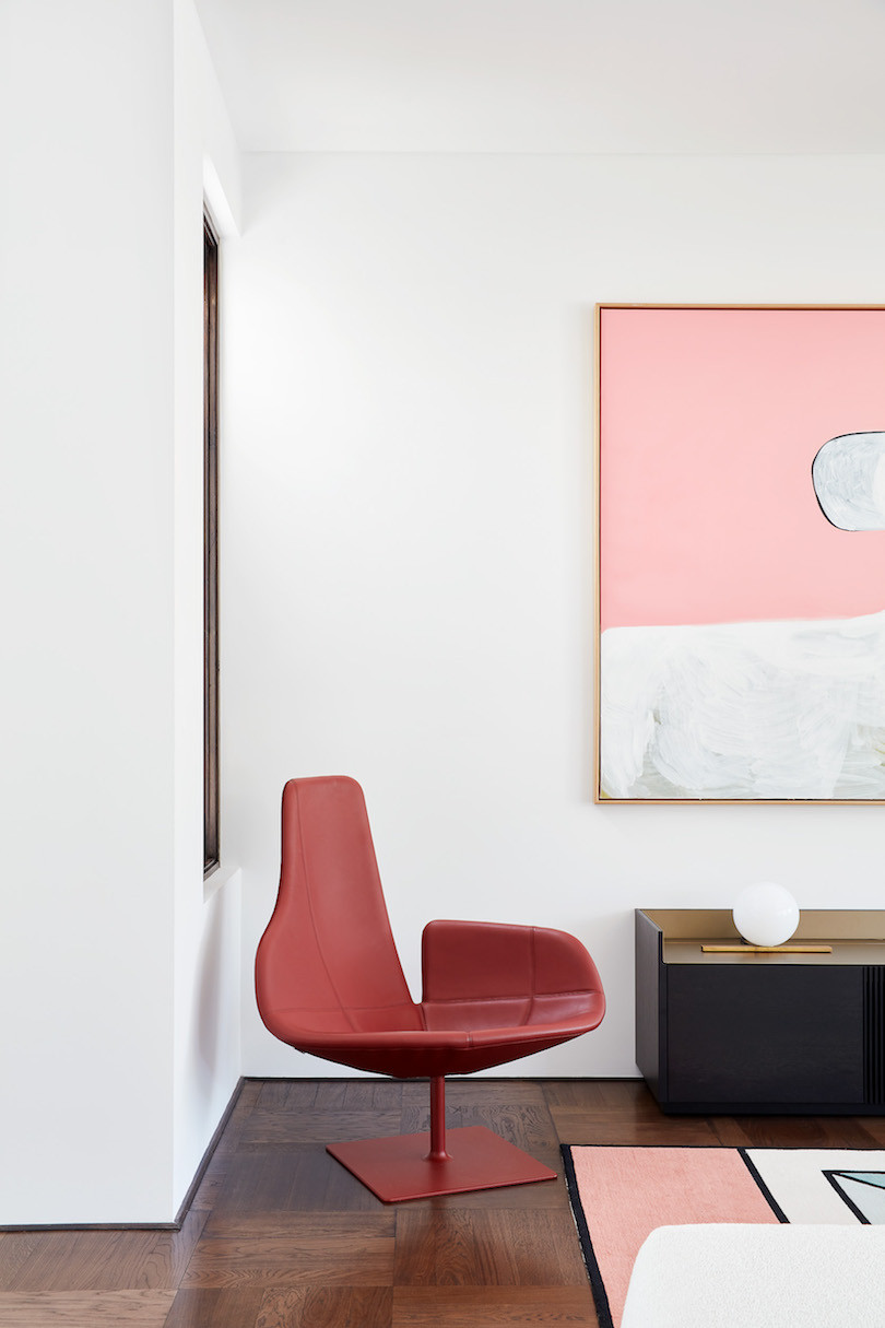 A red chair sits in the corner of the living room in State of Kin's Shutter House