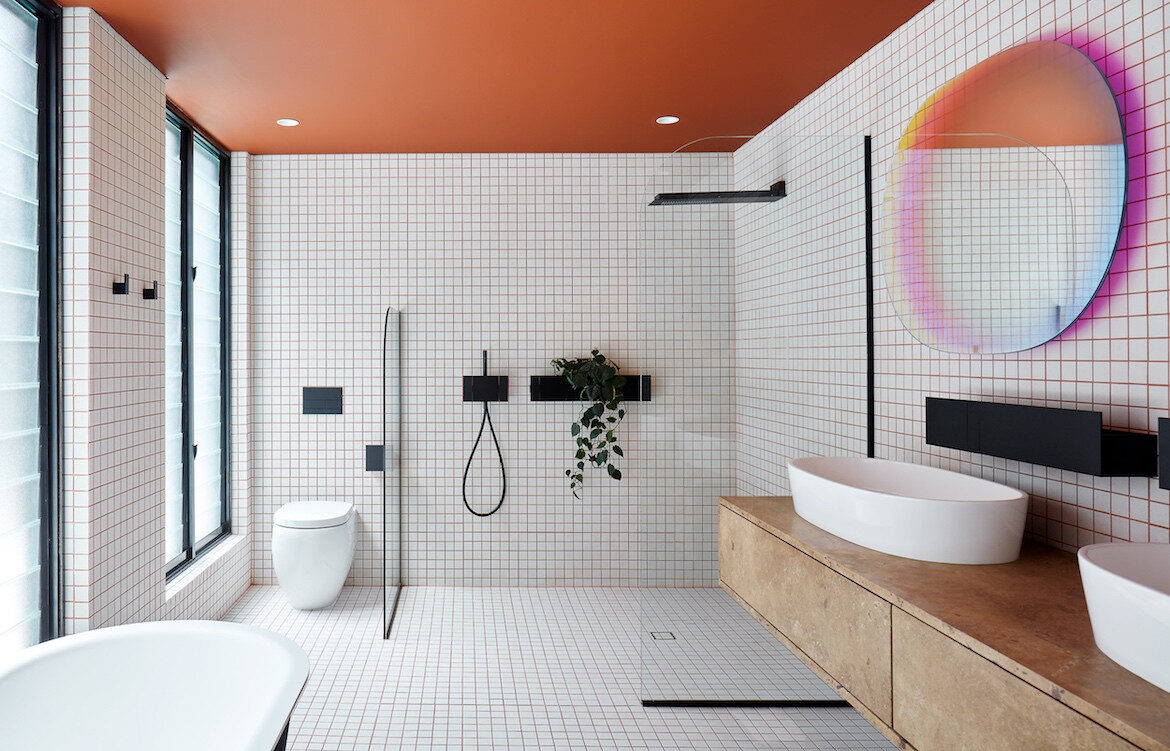 The white and orange bathroom with an iridescent mirror by Patricia Urquiola in State of Kin's Shutter House