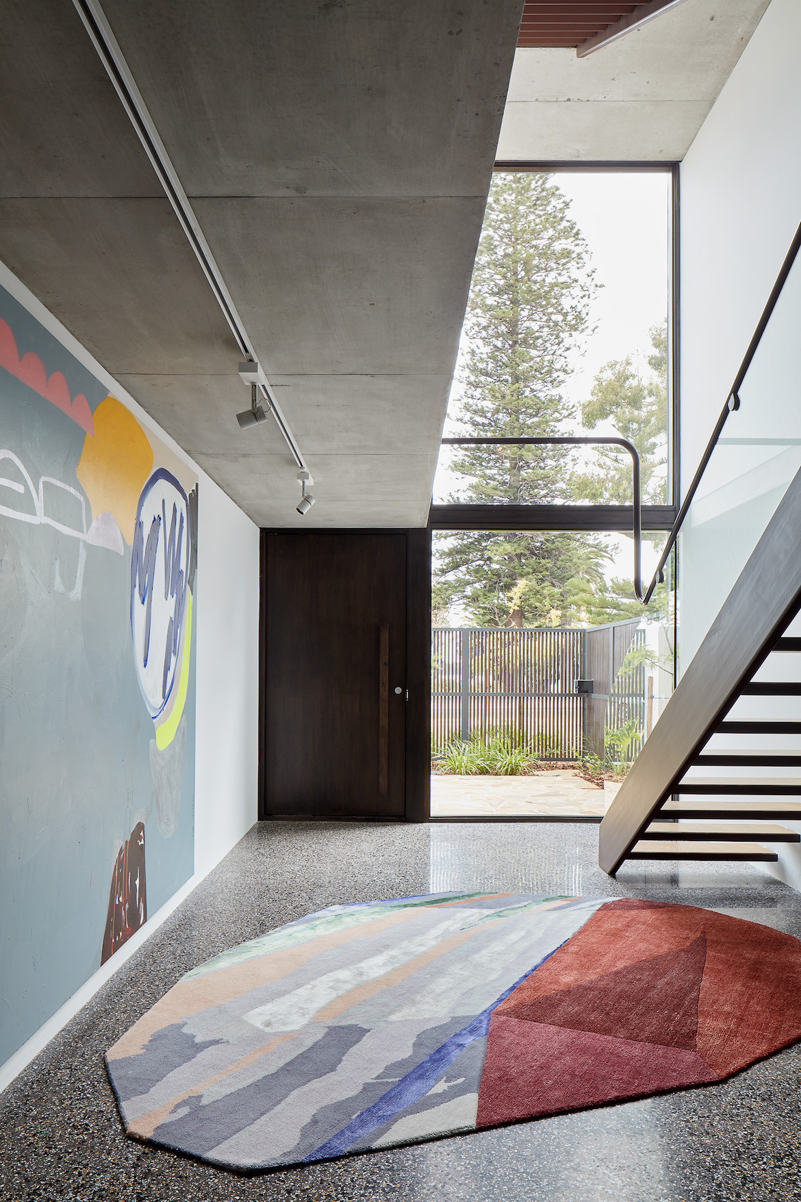 The entrance foyer to State of Kin's Shutter House with a painting by Elle Campbell and rug by Patricia Urquiola for cc-tapis