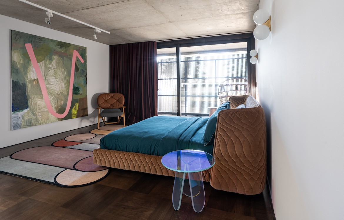 The master bedroom in A white couch and rug by Patricia Urquiola State of Kin's Shutter House