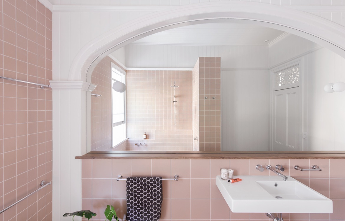 A traditional archway frames an expansive mirror in the pale pink Queenslander bathroom.