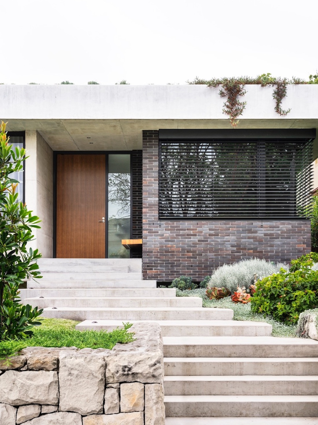 A stone pathway leads up to the home's wooden front door.