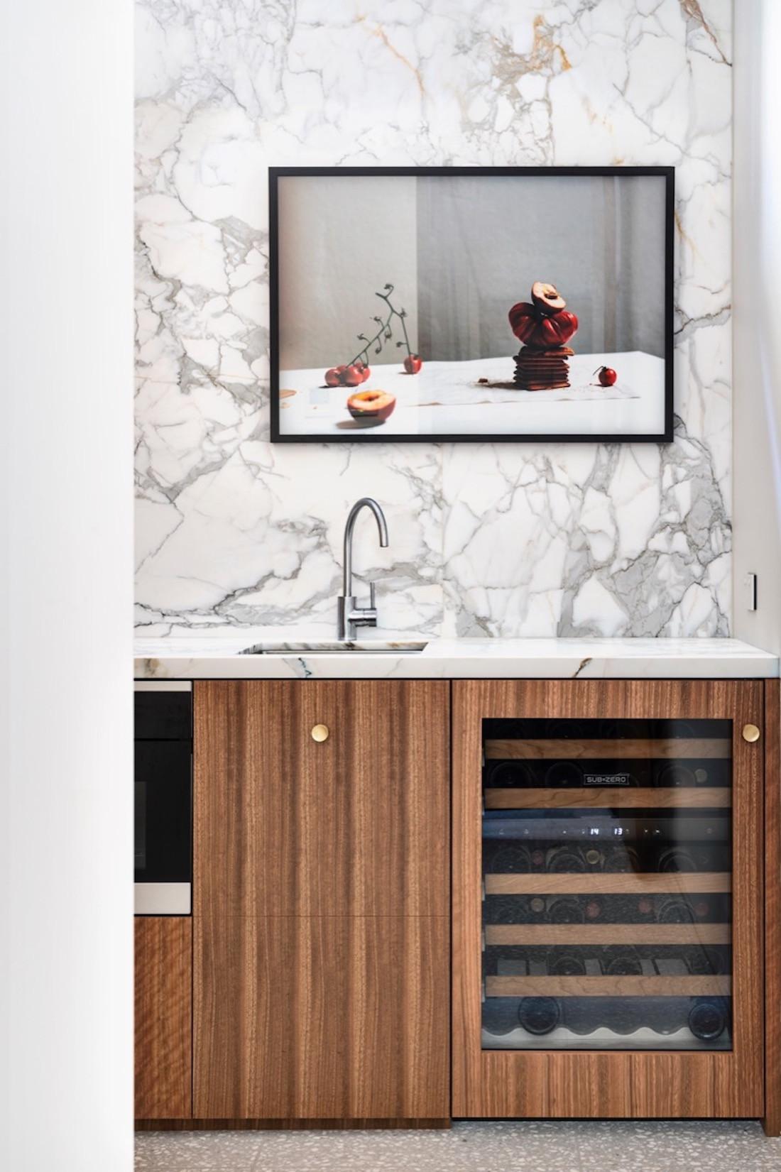 A wine fridge is encased in timber veneer and sitting under an artwork.