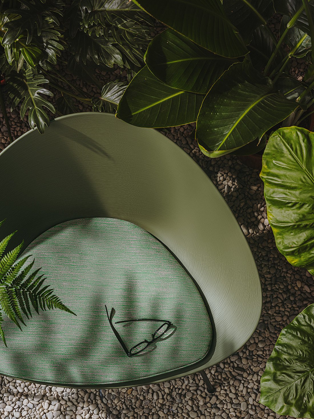 An olive green polypropylene Adell lounge chair by Arper is surrounded by green folliage.