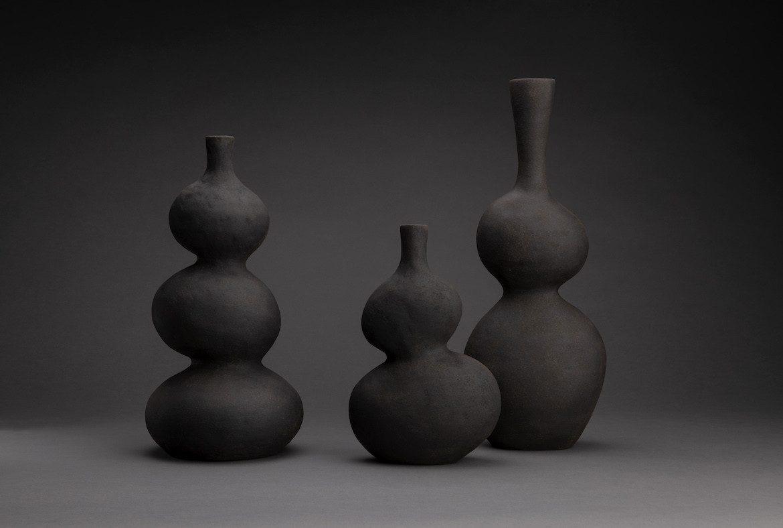 Three of Eloise White's black ceramic vessels on a black background.