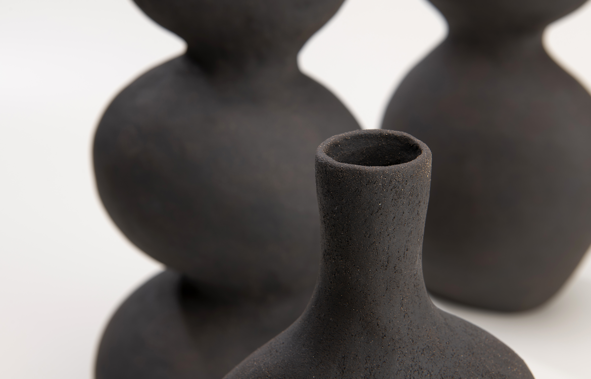 A close up showing the texture of a black ceramic vessel by Eloise White.