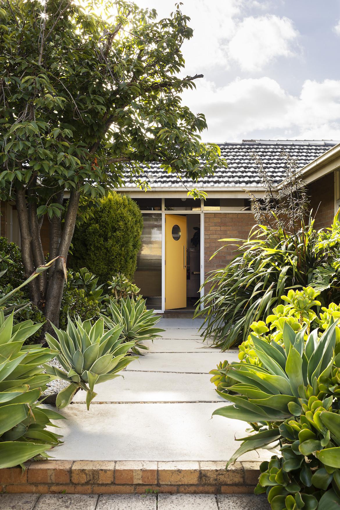 The yellow front door of the brick home stands slightly ajar.