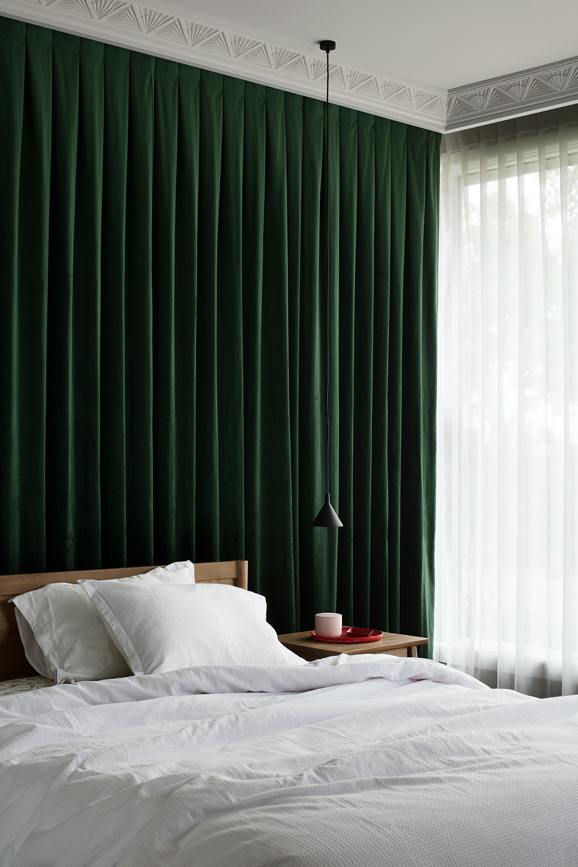 The master bedroom's white bedding and forest-green curtains.