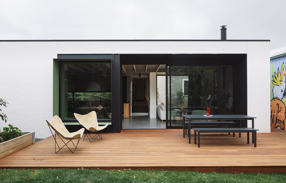 The extension's exterior verandah with deck chairs and table.