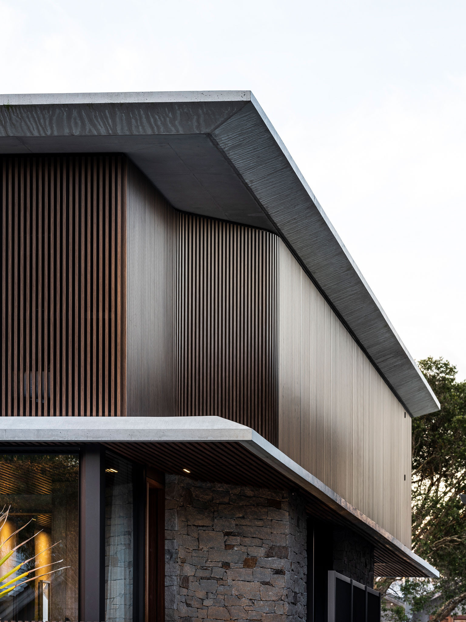 Designed by DKO, two townhouses in Manly, Sydney, showcase a robust yet refined exterior palette of concrete and dark timber shading devices, elevating the coastal influences of the locale.