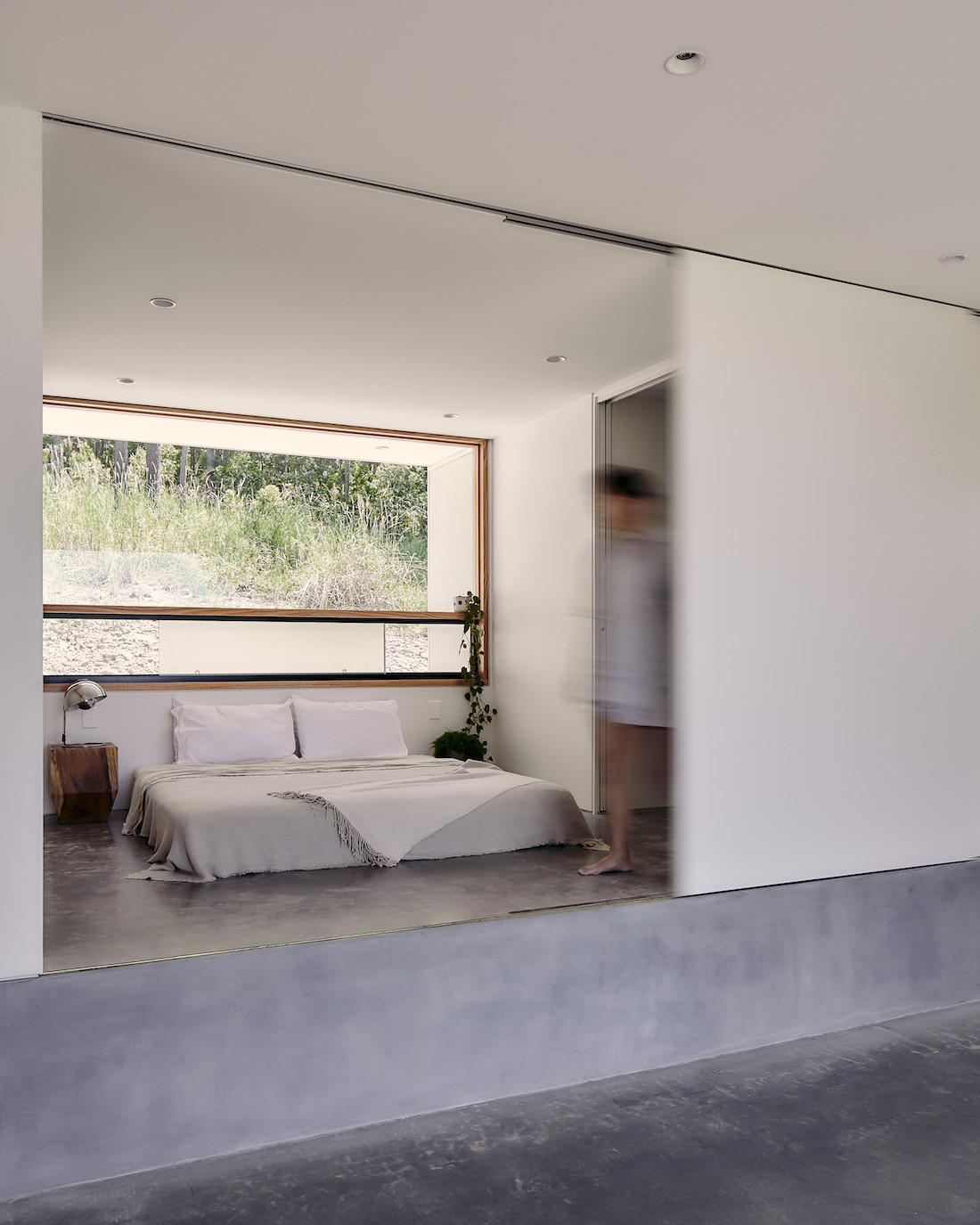 A bed sits on raised, polished concrete floor of the A-CH Yandina Sunrise home.