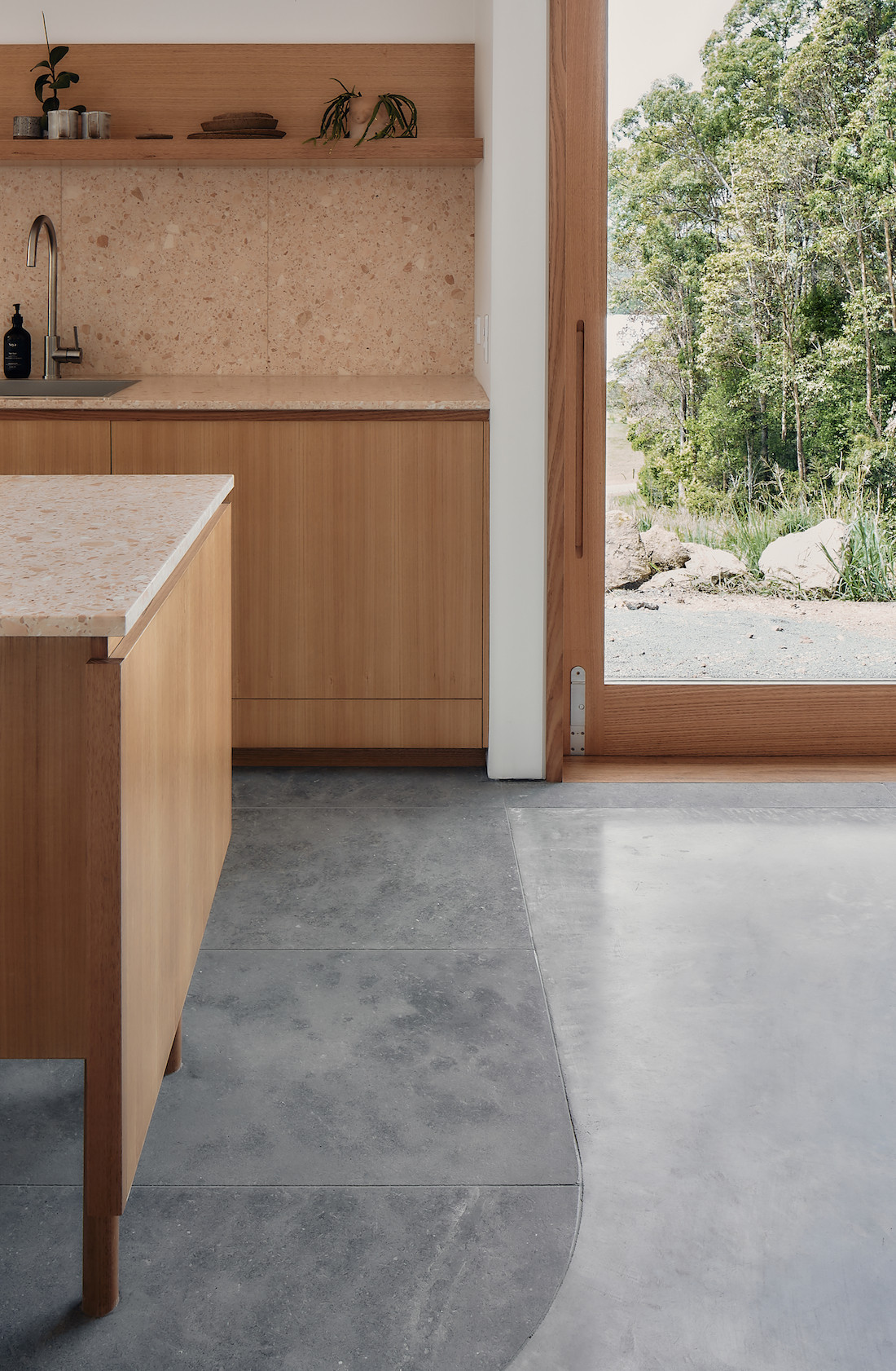 Limestone and concrete floors meet at the edge of the kitchen in A-CH's Yandina Sunrise Sunshine Coast hinterland home.