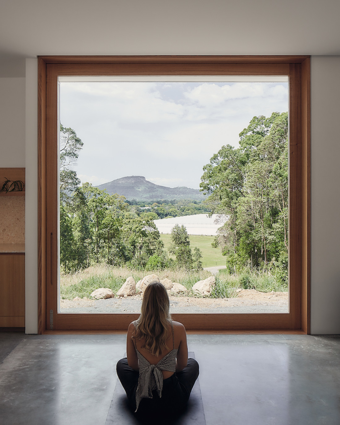 A person sits inside A-CH's Yandina Sunrise home, looking out a large window.