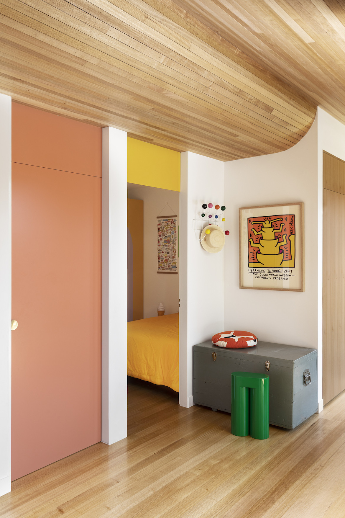 One pink door is closed, another is open to show a glimpse of one child's bedroom.