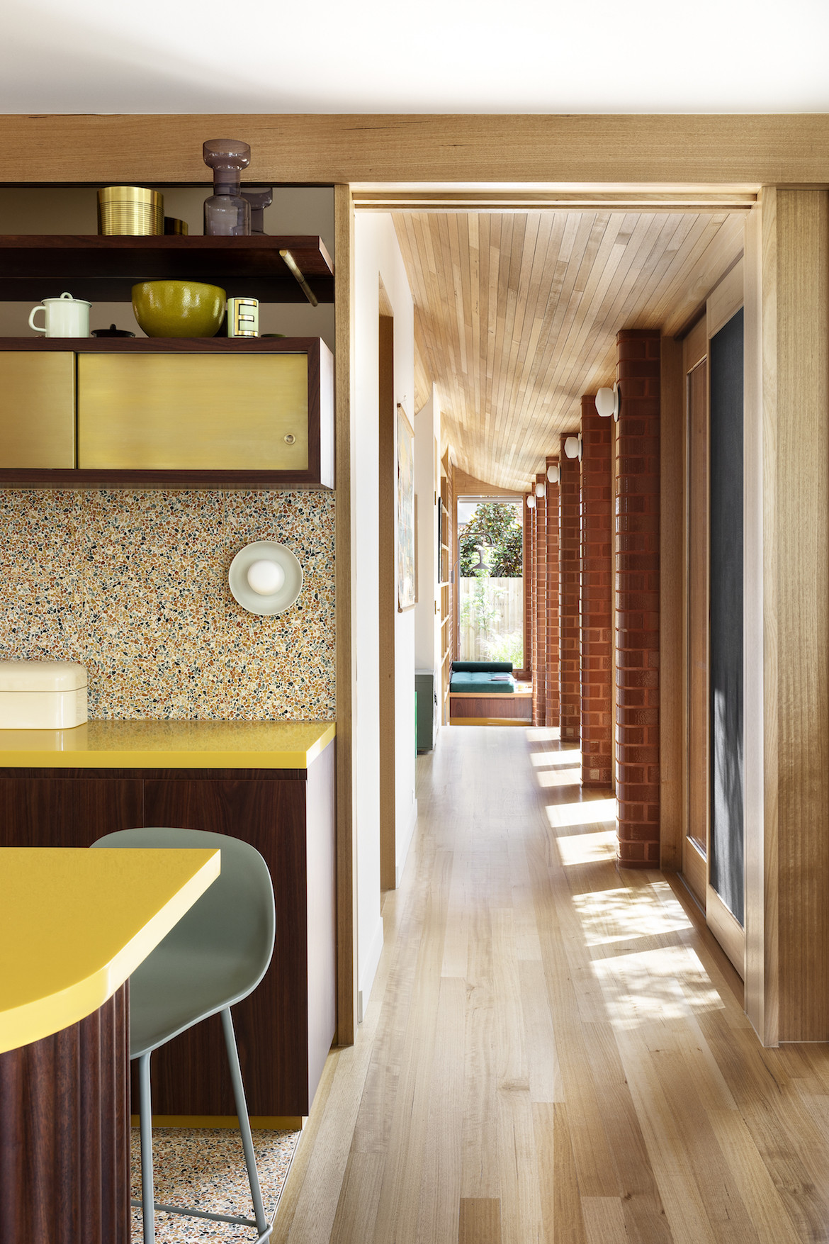 A view down the hallway with a slanted wooden roof and the edge of the kitchen's yellow bench and colourful terrazzo.