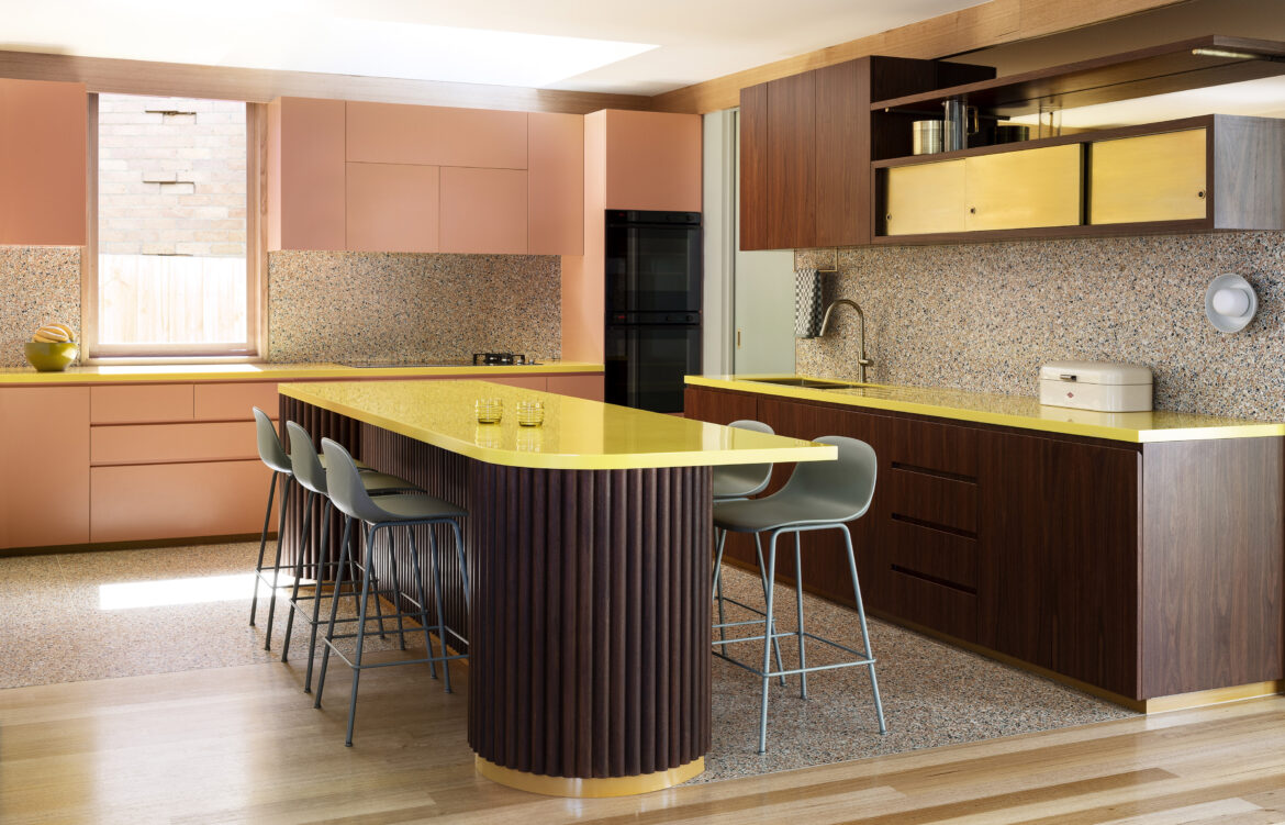 Colourful kitchen with yellow benches, pink cabinets and terrazzo floors by Wowowa