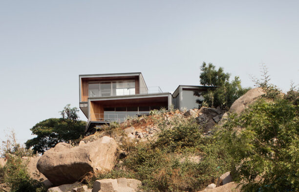 The Lakehouse by CollectiveProject hides atop the hills of Hyderabad, India, overlooking HiTec City and the Durgam Cheruvu Lake