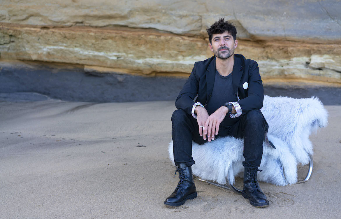 Léo Terrando seated on a beach in front of a stone wall