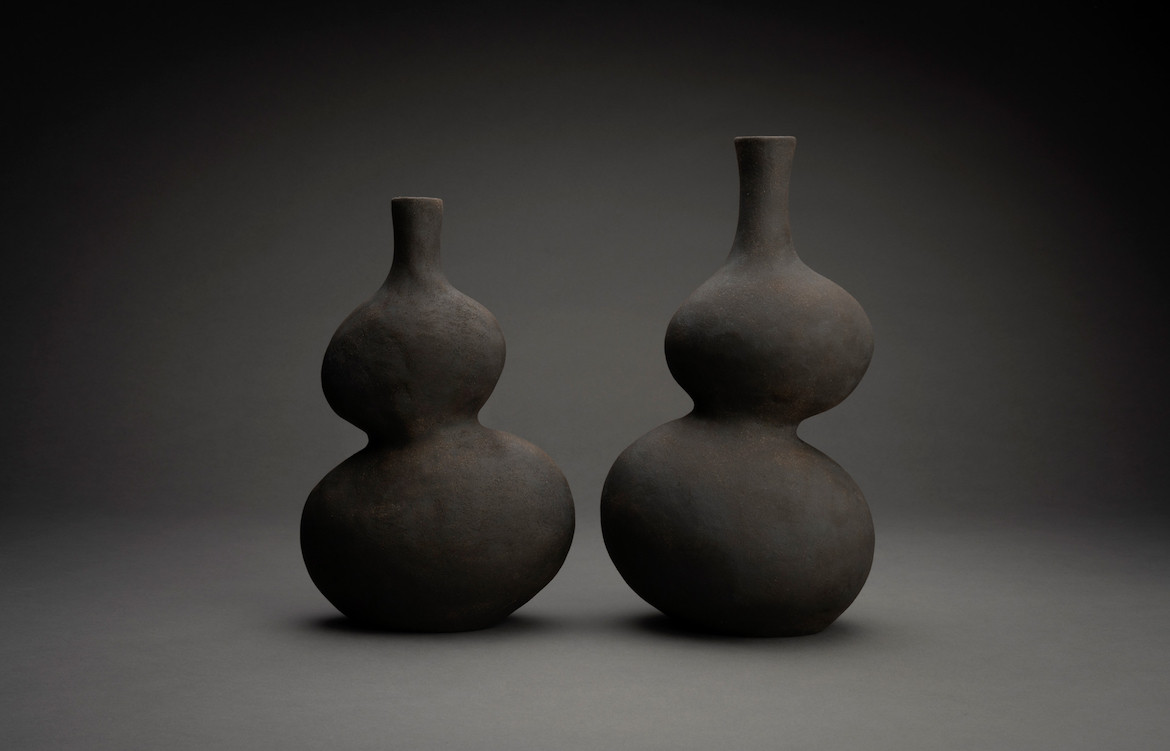 Two of Eloise White's black ceramic vessels on a black background.