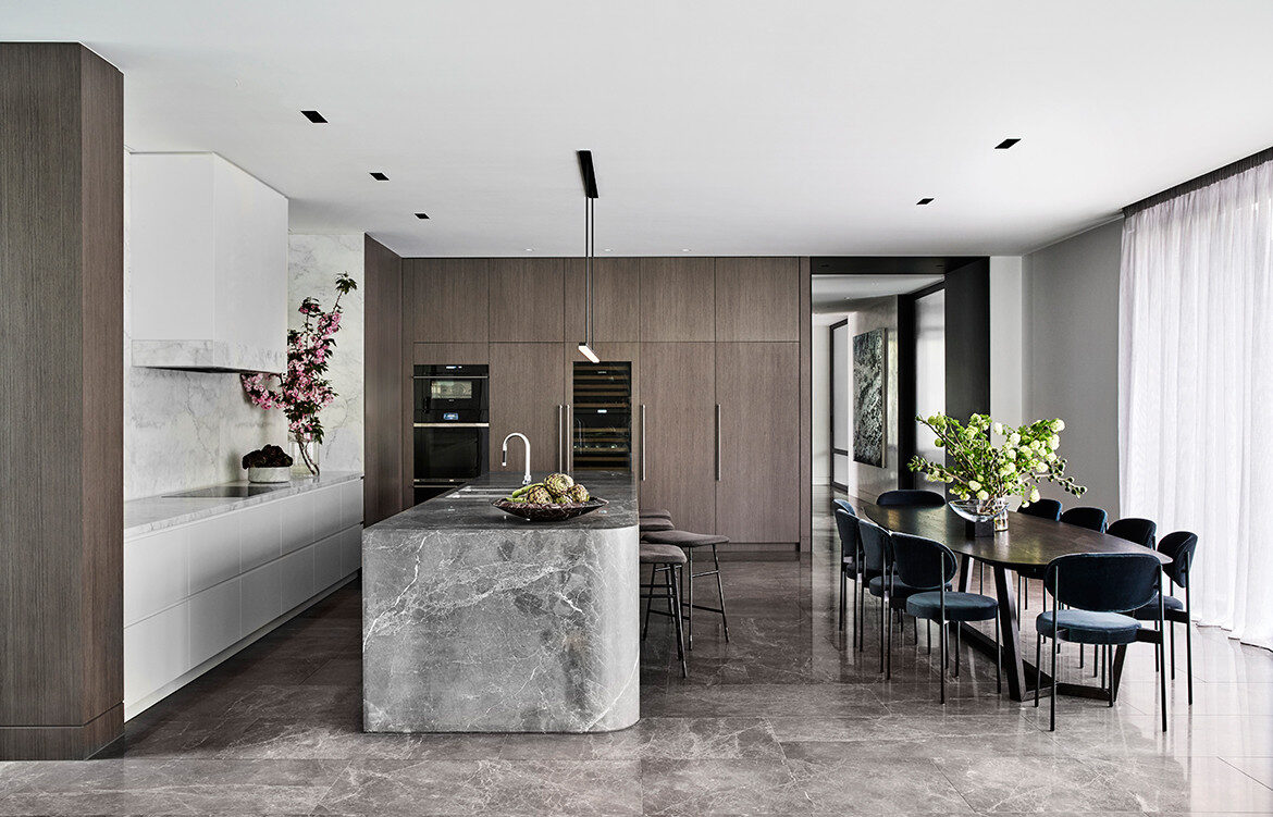 NNH Residence interior design by Mim Design contemporary open-plan kitchen and dining area with natural stone bench and dark cabinetry