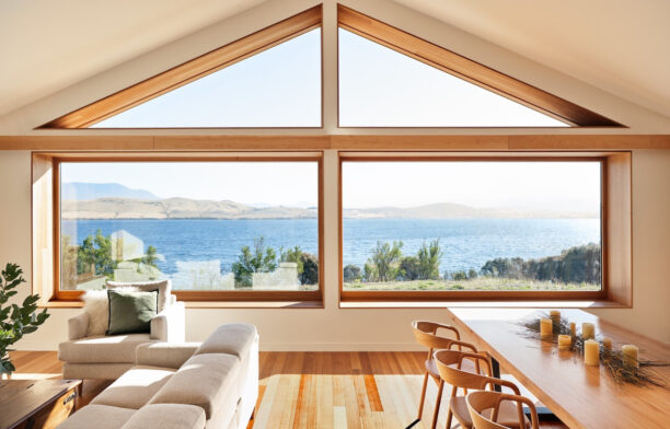 Four large windows with a triangle roof looking out over the bay from Thinking Paddock House by Open Creative Studio.