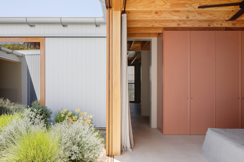 A bedroom with salmon coloured built-ins that looks onto the courtyard of Tribe Studio Architect's Bundeena Kit-home.