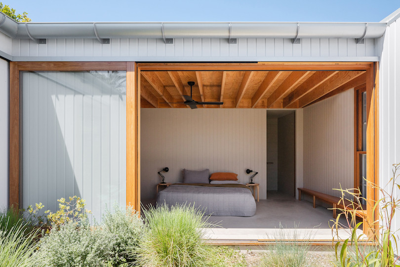 A bedroom that looks onto the courtyard of Tribe Studio Architect's Bundeena Kit-home.