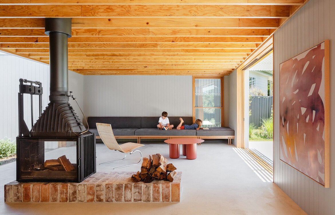 Two kids sit on the couch of the large open-plan living area in Tribe Studio Architect's Bundeena Kit Home.