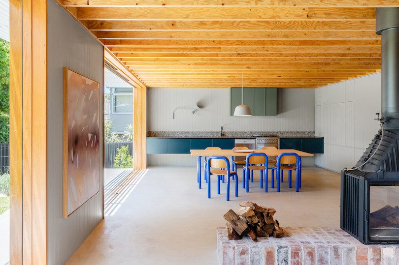 Six blue-framed chairs surround a dining table in the open-plan living room/kitchen of Tribe Studio Architect's Bundeena Kit-Home.