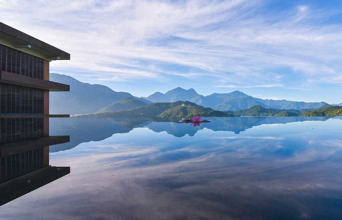 A blue sky and green mountains reflect on a spa.