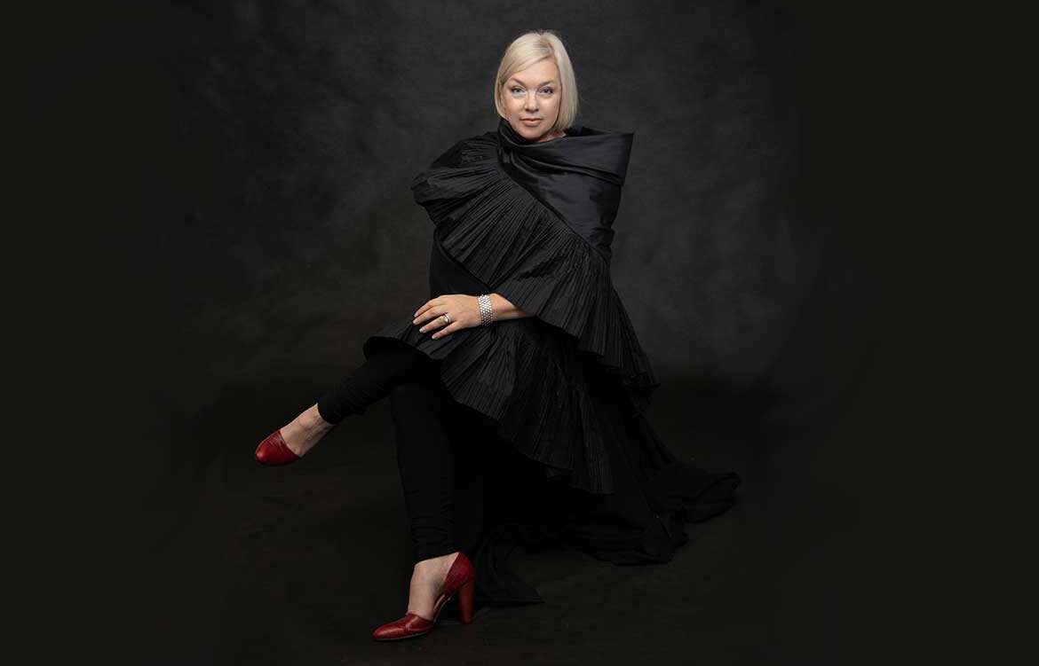 Christine McKanna Farr of designmilkstudio sits, wearing a black dress and red heels in front of a black background.